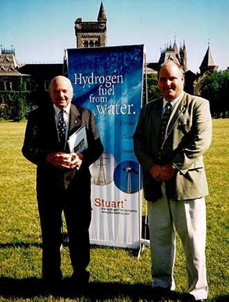 A picture of Alexander K. Stuart and Andrew Stuart standing in fron of a hydrogen production flag