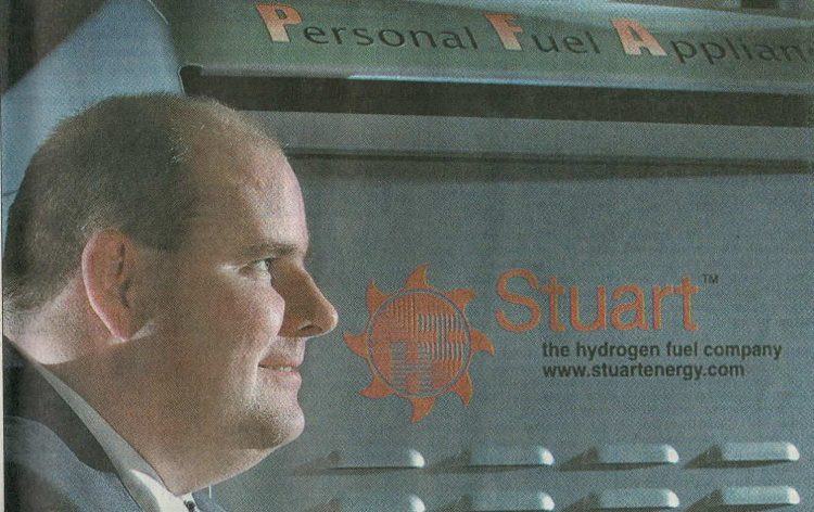 A picture of Andrew T.B. Stuart standing in front of the Personal Fuel Appliance
